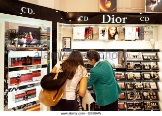 Woman-shopping-for-dior-cosmetics-duty-free-shop-dubai-airport-departure-dx90aw