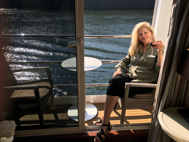 NANCY ENJOYING A GLASS OF WINE ONBOARD